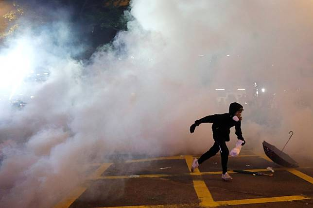 An anti-extradition demonstrator runs away from tear gas, after a march to call for democratic reforms, in Hong Kong, China July 21, 2019. Picture taken July 21, 2019.