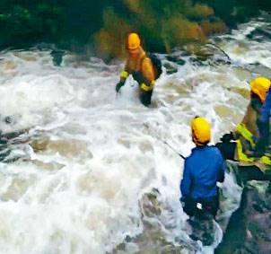 ■六名行山男女被困黃龍石澗,消防員在洪水中救援。