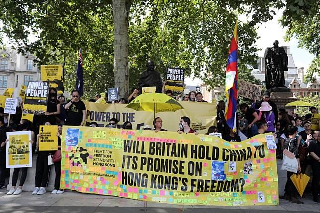 在倫敦,聲援香港示威者的人士舉起標語。(法新社圖片)
