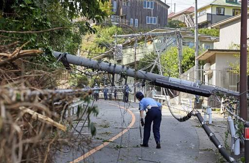 A police officer ispects a fallen utility pole downed by winds caused by Typhoon Faxai in Kamakura, Kanagawa prefecture on September 9, 2019. The powerful typhoon that battered Tokyo overnight with ferocious winds killed two people, police said on September 9, as halted trains caused commuter chaos and more than 100 flights were cancelled.