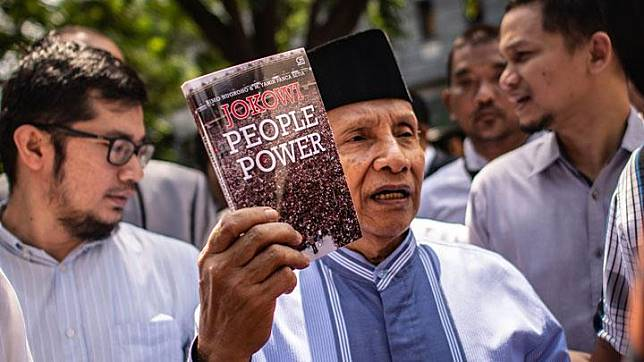 Ketua Dewan Kehormatan PAN Amien Rais menunjukkan buku berjudul Jokowi People Power saat jeda pemeriksaan untuk salat Jumat, di Polda Metro Jaya untuk memenuhi panggilan, Jakarta, 24 Mei 2019. ANTARA