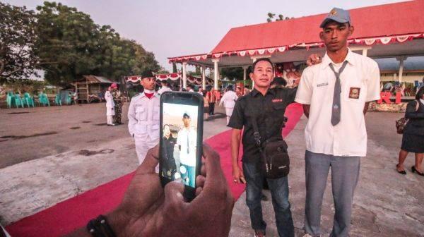 Seorang warga berfoto bersama Kristoforus Sina, siswa kelas 2 SMU yang bertinggi badan 197 cm
