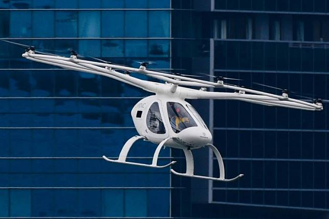 A Volocopter unmanned air taxi transport flies over Marina Bay during test flight with a safety pilot at the 26th Intelligent Transport Systems World Congress (ITSWC) in Singapore on October 22, 2019.