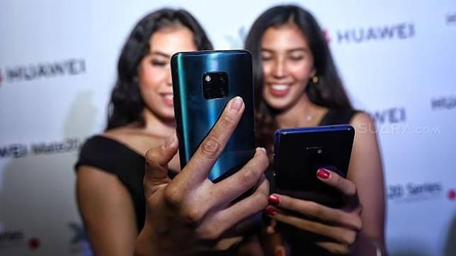 Model mencoba smartphone terbaru Mate 20 Series dari Huawei saat peluncuran perdana di Hotel Westin, Jakarta, Rabu (19/12). [Suara.com/Muhaimin A Untung]