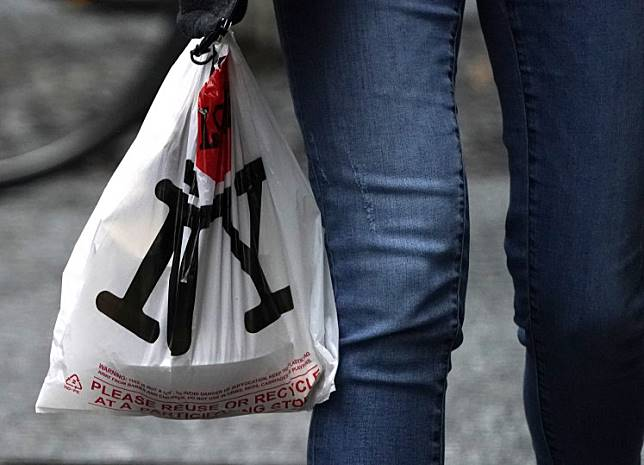 A person with their lunch in a plastic bags walks in midtown in New York on February 28, 2020, ahead of the statewide ban on plastic bags that takes effect March 1.