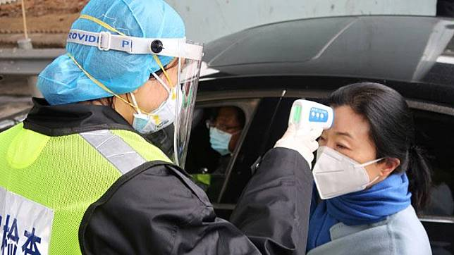 A security officer in a protective mask checks the temperature of a passenger following the outbreak of a new coronavirus, at an expressway toll station on the eve of the Chinese Lunar New Year celebrations, in Xianning, a city bordering Wuhan to the north, Hubei province, China January 24, 2020. REUTERS/Martin Pollard