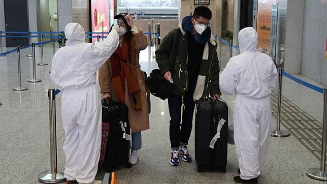 Workers in protective suits check the temperature of passengers arriving at the Xianning North Station on the eve of the Chinese Lunar New Year celebrations, in Xianning, a city bordering Wuhan to the north, in Hubei province, China January 24, 2020. The virus originated in the central Chinese city of Wuhan in Hubei late last year and has spread to Chinese cities including Beijing and Shanghai, as well as the United States, Thailand, South Korea and Japan. REUTERS/Martin Pollard