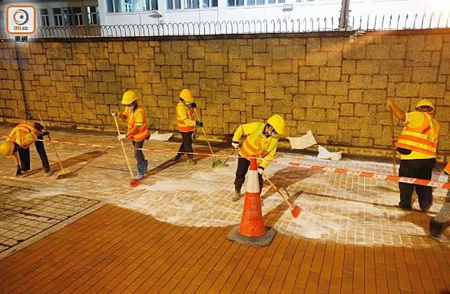 多名工人在地下鋪一層白沙。(黃偉邦攝)