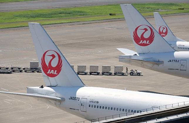 An airport employee works under passenger planes of Japan Airlines at Tokyo's Haneda airport on July 31, 2018.