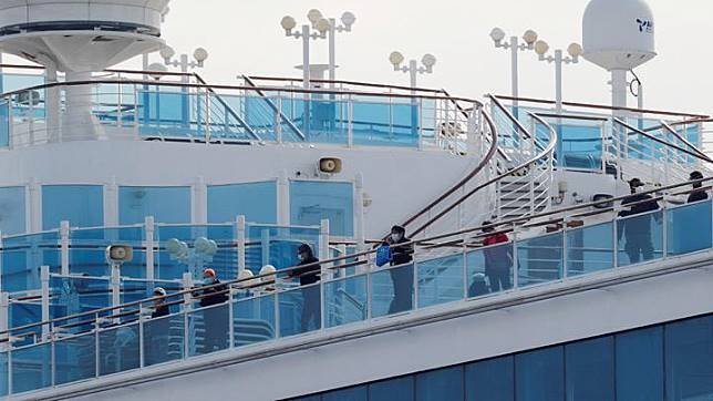 Passengers look out from a deck of the cruise ship Diamond Princess at Daikoku Pier Cruise Terminal in Yokohama, south of Tokyo, Japan February 12, 2020. Another 39 people have tested positive for the coronavirus on the cruise ship Diamond Princess quarantined in Japan, with one quarantine officer also infected, bringing the total to 175, the health ministry said on Wednesday. REUTERS/Kim Kyung-hoon