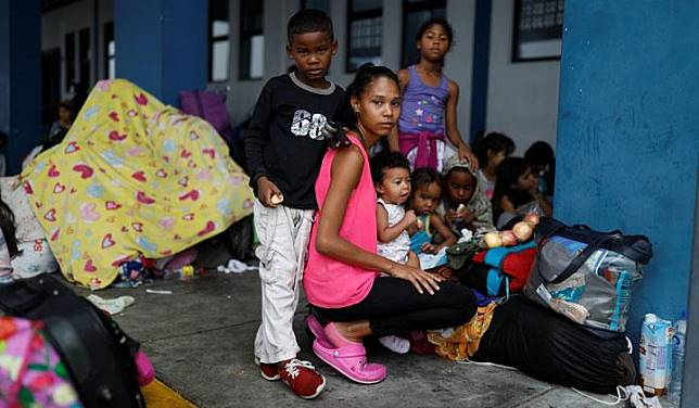 Venezuelan migrant Crisyesmil Rosales, 23, poses for a picture with her children Andres, 6, Aranza, 2,  Sara, 20 months, her sister Angeli, 8, and her brother Abraham, 6, while they wait to process their documents at the Ecuadorian-Peruvian border service center, before continuing their journey to Arequipa, on the outskirts of Tumbes, Peru, June 16, 2019. Rosales is travelling with her siblings, her children and an aunt. She said that after eight days travelling, the toughest thing of her journey has been to sleep with the children on the street.