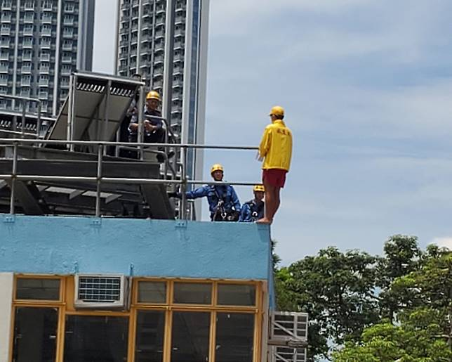 救生員站在欄桿外企圖從高處跳下。梁國峰攝