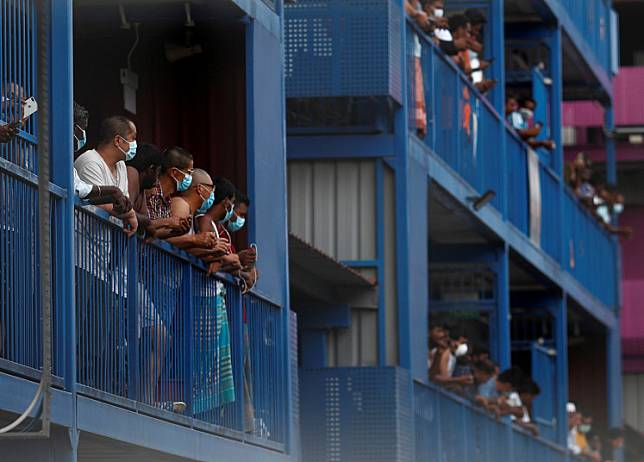 Workers from Bangladesh, India and China look out of their balconies during food distribution at Punggol S-11 workers' dormitory, which was gazetted to be an isolation facility after it became a cluster of COVID-19 cases, in Singapore April on Monday.