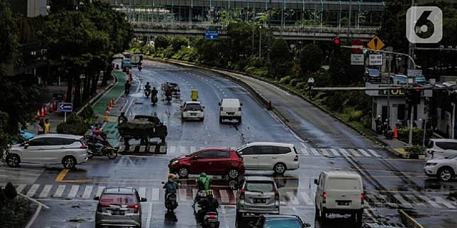 Kendaraan melintas di kawasan ganjil genap di jalan medan merdeka barat, Jakarta, Rabu (8/4/2020). Ditlantas Polda Metro Jaya mengumumkan perpanjangan masa peniadaan kebijakan pembatasan kendaraan bernomor polisi ganjil genap di wilayah Jakarta hingga 19