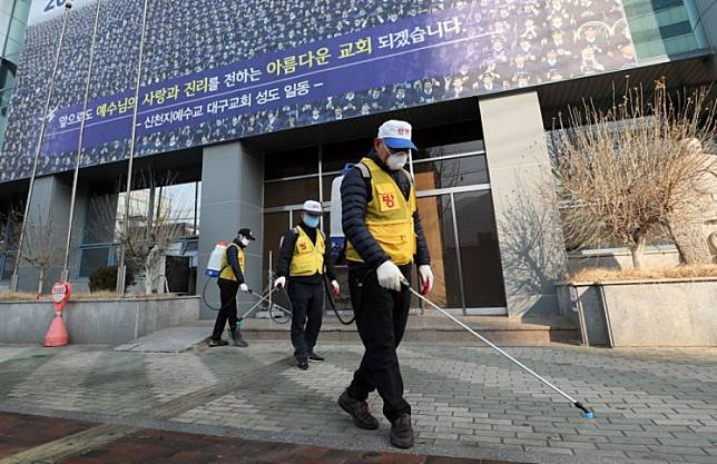 South Korean health officials spray disinfectant in front of the Daegu branch of the Shincheonji Church of Jesus in the southeastern city of Daegu on February 20, 2020 as about 40 new cases of the COVID-19 coronavirus confirmed after they attended same church services. - A cluster of novel coronavirus infections centred on a cult church in the South Korean city of Daegu leaped to 39 cases on February 20, as the country's total jumped for the second successive day.