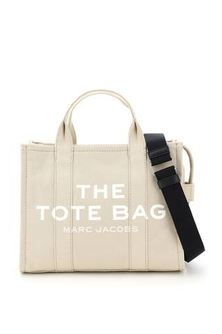 The Small Traveler Tote bag by Marc Jacobs in cotton canvas, featuring adjustable and removable webbing strap, contrast front logo print, back logo patch, zip closure, side handle. Unlined interior with one zip pocket and two small pockets. Steel-finish metalware.