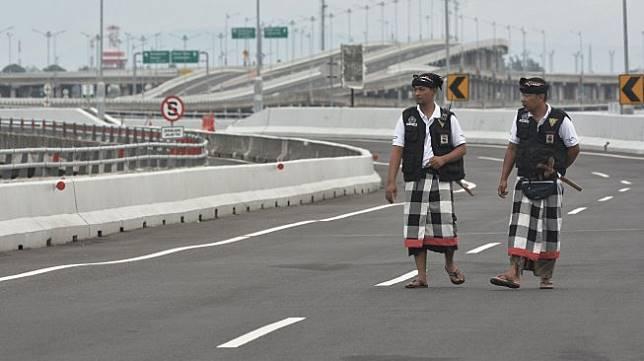 Pecalang atau petugas pengamanan adat Bali memantau situasi saat Hari Raya Nyepi Tahun Saka 1941 di kawasan Jalan Tol Bali Mandara, Bali, Kamis (7/3). [ANTARA FOTO/Fikri Yusuf]