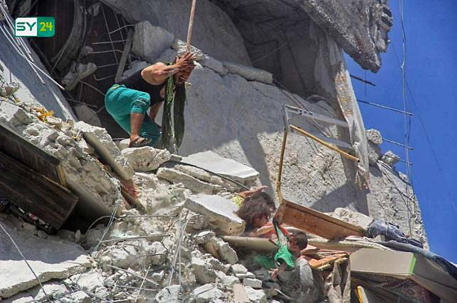 An image grab taken from a video by Syrian news website SY24 on July 24, 2019 shows a Syrian man reacting as two dust-covered Syrian girls, trapped in rubble, grab their baby sister from her shirt as she dangles from a bombed-out building in the Syrian town of Ariha in the northwestern province of Idlib. - Of the three girls shown in the photo, one is dead and two are fighting to stay alive, after regime airstrikes hit their home, said Dr Ismail, who treated the victims in a nearby hospital. Riham, 5, who appears in the photo gripping her sister's green shirt, died on Wednesday, the doctor said. Touka, the seven-months-old girl who is shown dangling in the air, is currently in intensive care, after suffering a trauma to the head, he added. Dalia, who also appears in the photograph, is stable after undergoing chest surgery, according to Mohamed, another doctor at the same facility. The girls are part of a family of eight, consisting of two parents and six sisters.
