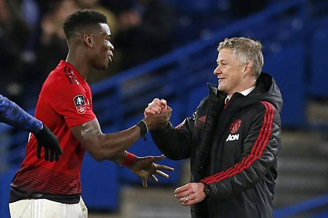 Manchester United's Norwegian caretaker manager Ole Gunnar Solskjaer (R) celebrates their victory with Manchester United's French midfielder Paul Pogba (L) on the pitch after the English FA Cup fifth round football match between Chelsea and Manchester United at Stamford Bridge in London on February 18, 2019. Manchester United won the game 2-0. Ian KINGTON