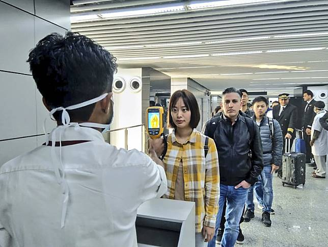 A man (left) uses a thermographic camera on Tuesday to screen people at Netaji Subhash Chandra Bose International Airport in Kolkata, India, following the Ministry of Health and Family Welfare's advisory to screen passengers arriving in India from China regarding the coronavirus (nCoV).