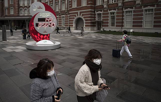 Pedestrians wearing face masks walk past the countdown clock for the upcoming Tokyo 2020 Olympic and Paralympic Games on February 26, 2020 in Tokyo.