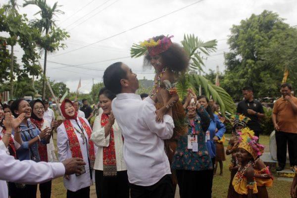 Presiden Joko Widodo menggendong salah satu anak PAUD TK Theresia di Kota Sorong, Papua Barat, Jumat (13/4)