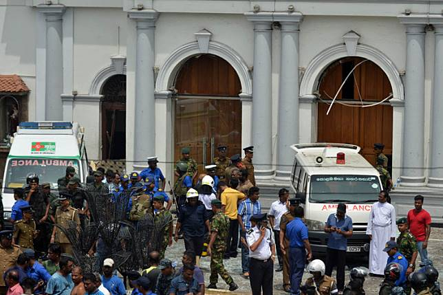 Ambulances are seen outside the church premises with gathered people and security personnel following a blast at the St. Anthony's Shrine in Kochchikade, Colombo on April 21, 2019. - At least 42 people were killed April 21 in a string of blasts at hotels and churches as worshippers attended Easter services, a police official told AFP. (Photo by ISHARA S. KODIKARA / AFP)