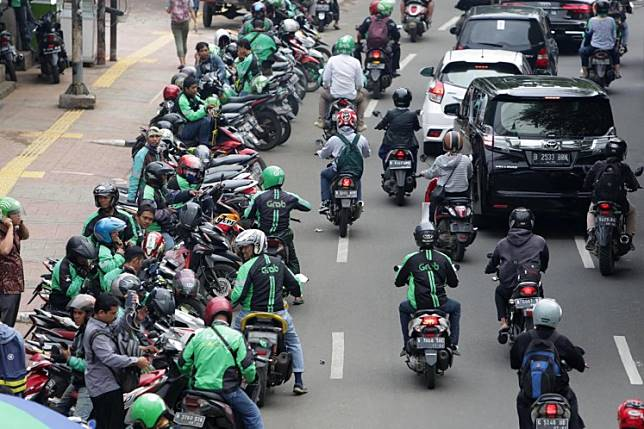App-based motorcycle 'ojek' taxi drivers wait for passengers on a road near Palmerah Station in Jakarta.