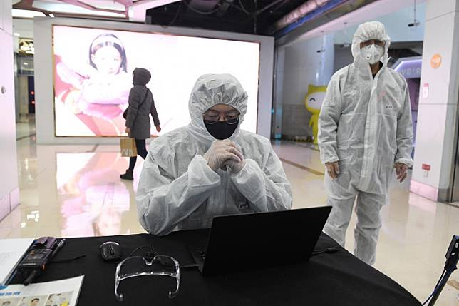 Security guards wear hazmat suits as a preventive measure against the COVID-19 coronavirus as they check the temperature of arriving customers at a shopping mall in Beijing on Feb. 27.