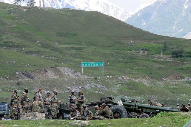 Indian army soldiers rest next to artillery guns at a makeshift transit camp before heading to Ladakh, near Baltal, southeast of Srinagar, June 16, 2020.China began pulling back troops from along its contested border with India on Monday, Indian government sources said, following a clash between the two countries last month in which 20 Indian soldiers were killed.