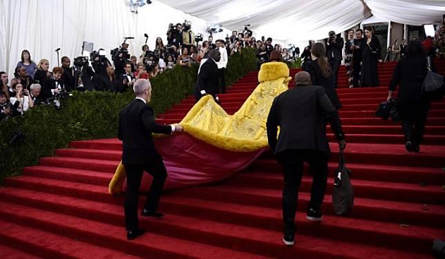 Rihanna tampak dari belakang saat sedang menapaki anak tangga Metropolitan Museum of Art, lokasi Met Gala 2015, dengan gaun kuning ikoniknya.