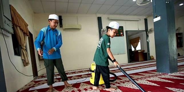 uhammad Fikri Aminuddin, 13, dan rakannya, Muhammad Aqil Iman Abdul Halim, 12, membersihkan surau (Foto: Harian Metro)