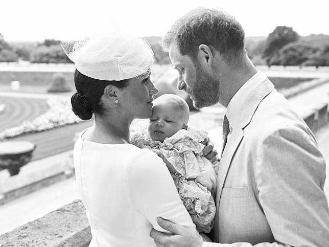 This official handout Christening photograph released by the Duke and Duchess of Sussex shows Britain's Prince Harry, Duke of Sussex (R), and his wife Meghan, Duchess of Sussex holding their baby son, Archie Harrison Mountbatten-Windsor at Windsor Castle with the Rose Garden in the background, west of London on July 6, 2019.