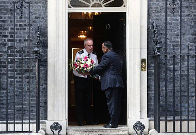 A man delivers flowers to 10 Downing Street after British Prime Minister Boris Johnson was moved to intensive care after his coronavirus (COVID-19) symptoms worsened and Secretary of State for Foreign affairs Dominic Raab was asked to deputise, London, Britain, on Tuesday.