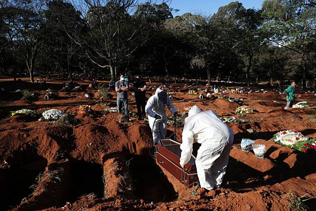 Gravediggers wearing protective suits prepare to bury the coffin of Izolina de Sousa, 85, who died from the COVID-19, at Vila Formosa cemetery, Brazil's biggest cemetery, in Sao Paulo, Brazil, May 26, 2020.