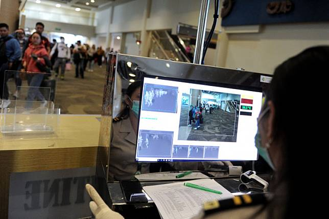 An official monitors passengers using a thermal scanner at an arrival gate at Ngurah Rai International Airport in Denpasar, Bali, on Jan. 22. The scanner was set up to detect a deadly coronavirus that emerged from Wuhan, China.