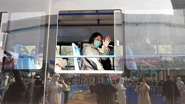 Pasien yang sembuh dari virus Corona melambaikan tangan saat meninggalkan rumah sakit sementara Wuchang di Wuhan, Provinsi Hubei, Cina, 10 Maret 2020. Sementara itu, 16 rumah sakit sementara di Wuhan resmi ditutup pada Selasa (10/3) seiring menurunnya jumlah pasien terinfeksi virus Corona. Xinhua/Wang Yuguo