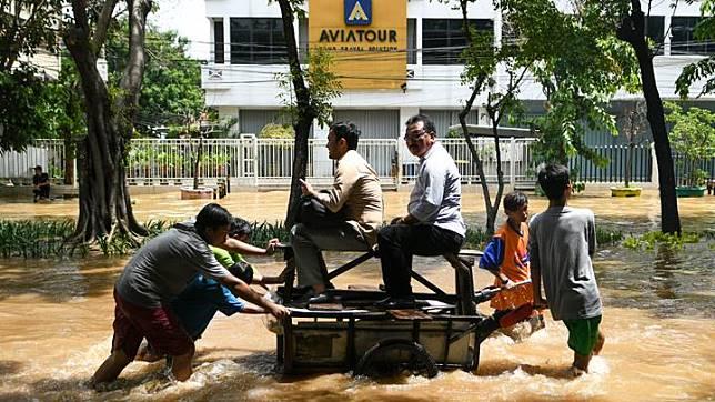 Dua orang warga menaiki gerobak yang didorong sejumlah anak saat melintasi genangan banjir di kawasan Jalan Bungur Besar Raya, Jakarta, Kamis 2 Januari 2020. Berdasarkan data Badan Nasional Penanggulangan Bencana (BNPB) per 2 Januari 2020, terdapat 63 titik banjir di wilayah DKI Jakarta dan secara keseluruhan terdapat 169 titik banjir untuk Jabodetabek dan Banten. ANTARA FOTO/M Risyal Hidayat