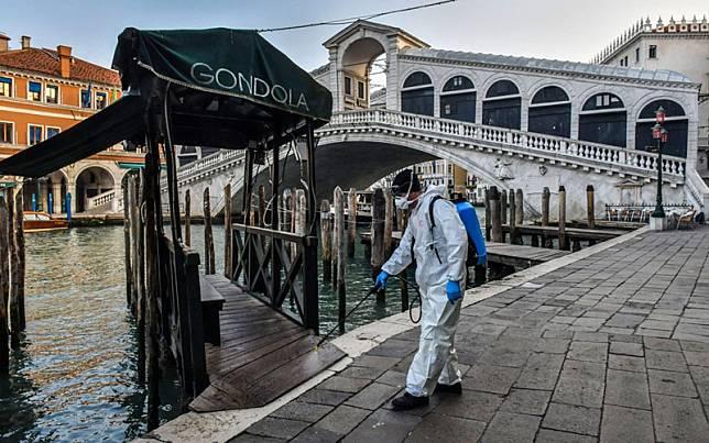 Seorang pria menyemprotkan disinfektan untuk mematikan virus corona di kota air Venesia, Italia./Bloomberg