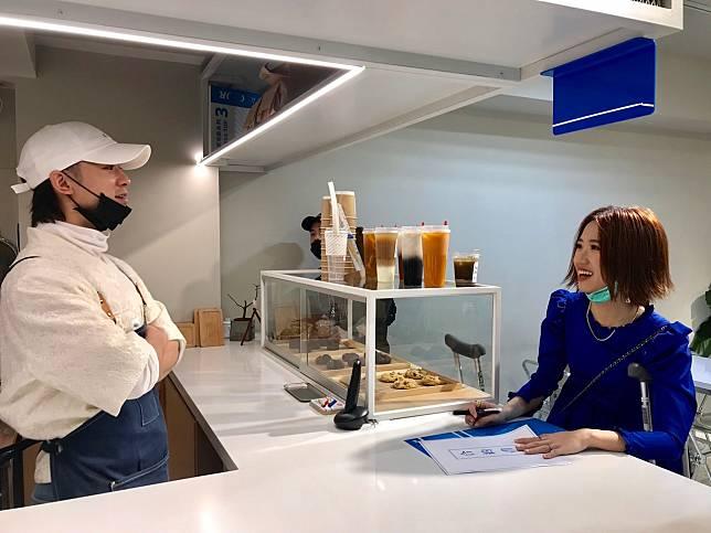 Lulu(右)柱著枴杖出門和吳思賢簽約賣咖啡。記者葉君遠/攝影