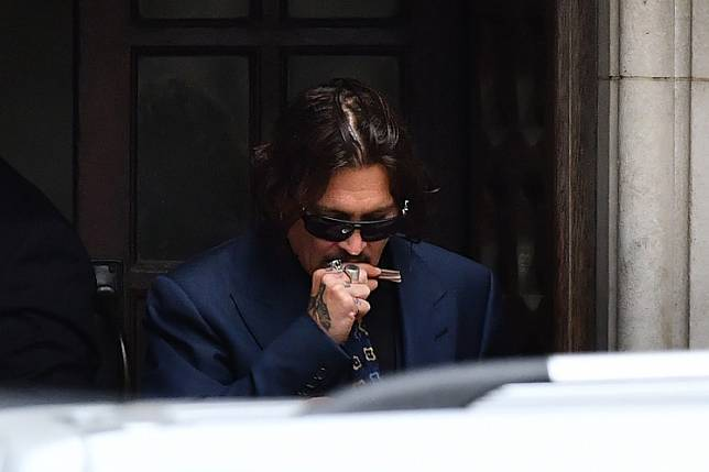 US actor Johnny Depp gestures as he leaves on the third day of his libel trial against News Group Newspapers (NGN), at the High Court in London, on July 9, 2020.