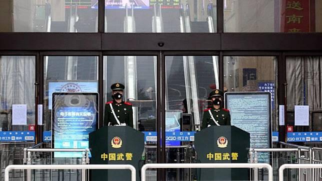 Petugas paramiliter Cina mengenakan masker sedang berjaga di pintu masuk Stasiun Kereta Api Hankou yang ditutup setelah kota itu dikarantina karena merebaknya virus corona baru di Wuhan, provinsi Hubei, Cina 23 Januari 2020.[China Daily via REUTERS]