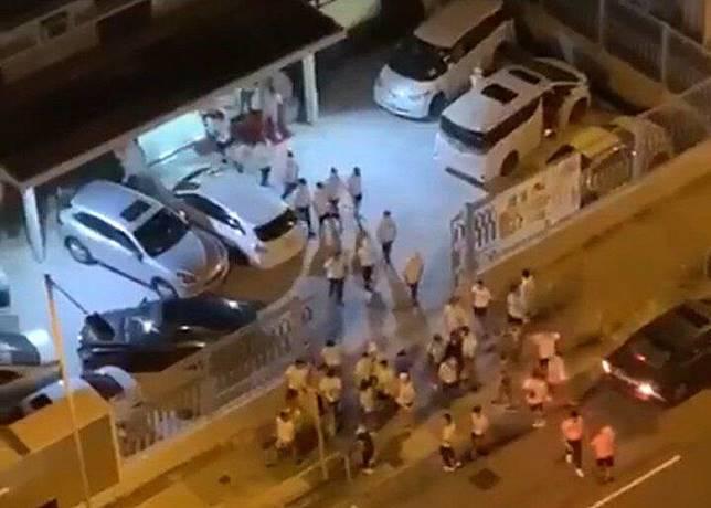 大批穿白衣的男子在屯門鄉事會行政大樓對開聚集。(互聯網)