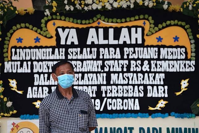 A man wearing a face mask stands in front of a flower board, which bears a message of support for staff of Sulianti Saroso Infection Diseases Hospital in Jakarta on March 21.