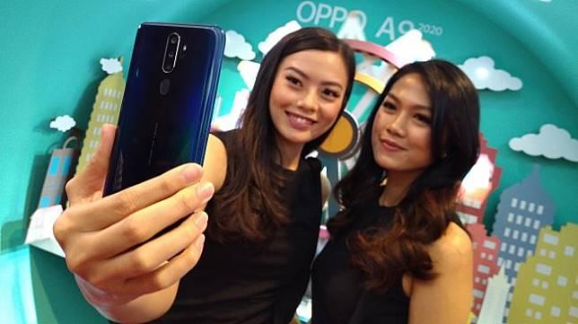 Dua orang model sedang berfoto menggunakan ponsel Oppo A 2020 di Jakarta, Selasa (17/9/2020). [Suara.com/Tivan Rahmat]