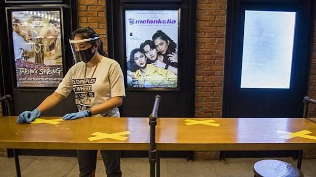 Pekerja memasang tanda jaga jarak saat simulasi pembukaan dan peninjauan tempat hiburan bioskop CGV Cinemas di Bandung Electronic Center (BEC), Bandung, Jawa Barat, Kamis (9/7). [ANTARA FOTO/M Agung Rajasa]