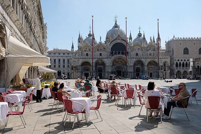Tourists are seen at the Caffe Quadri at St. Mark's Square a day before Italy and neighbouring EU countries open up borders for the first time since the COVID-19 outbreak hit the country, in Venice, Italy June 14, 2020.