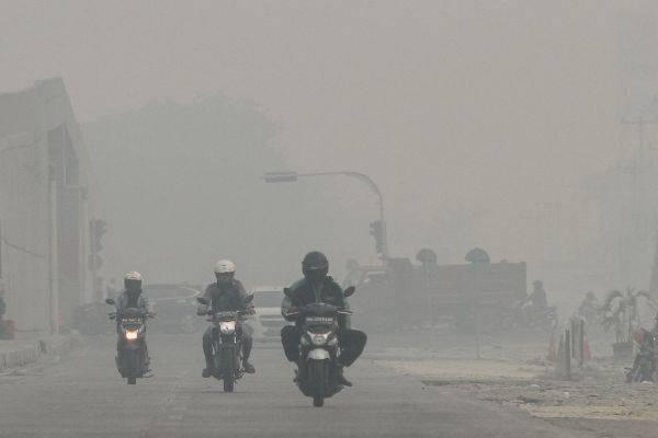 Pengendara kendaraan bermotor melintas di jalan Soekarno Hatta ketika kabut asap pekat dampak karhutla menyelimuti Kota Pekanbaru, Riau