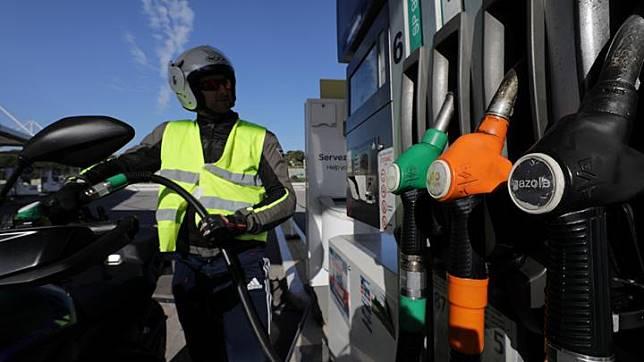 Seorang pengendara sepeda motor yang mengenakan rompi kuning atas simbol protes kenaikan harga bahan bakar minyak, mengisi tangkinya di sebuah pompa bensin di Antibes, Prancis, 17 November 2018. Para pengunjuk rasa berteriak agar Macron, yang baru memerintah selama 18 bulan ini, mengundurkan diri. REUTERS/Eric Gaillard