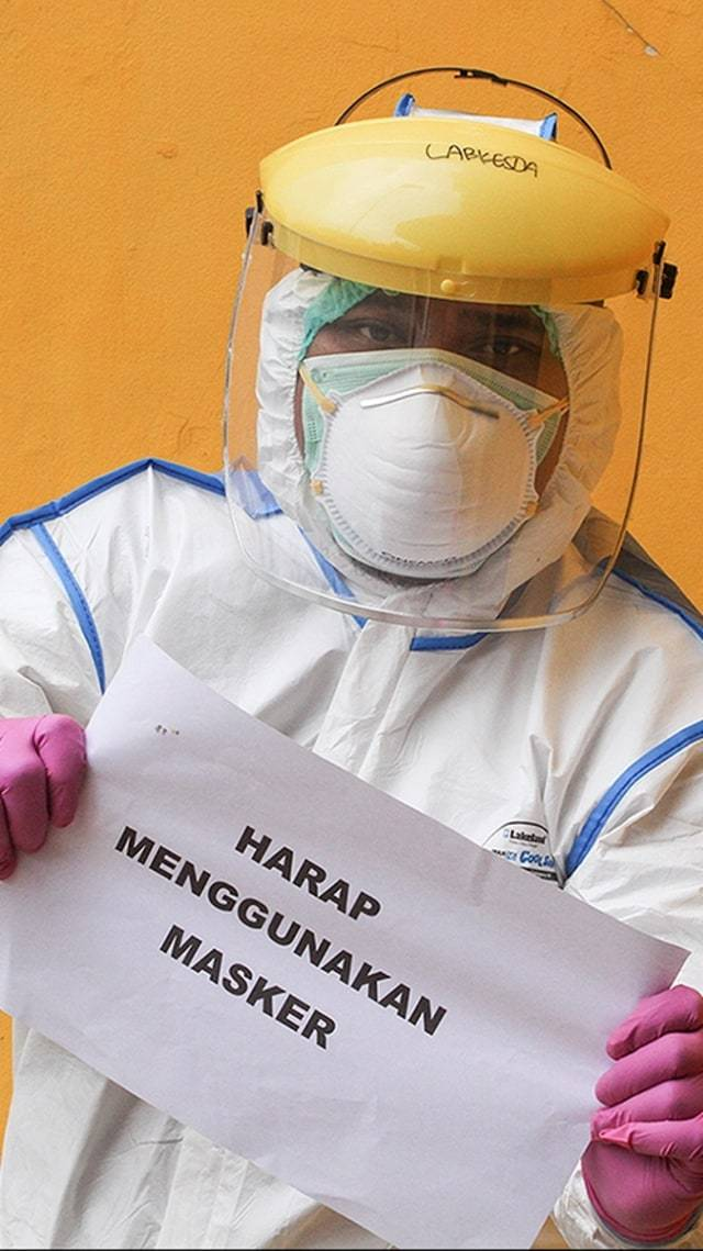 Petugas medis menunjukkan imbauan untuk masyarakat terkait virus corona seusai melaksanakan SWAB Test di Cimanggis, Depok, Jawa Barat, Minggu (8/4). Foto: ANTARA FOTO/Asprilla Dwi Adha